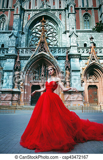 Beautiful girl in long red dress and in royal crown nearly catholic cathedral