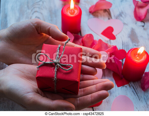 Female hands making red gift. Love and valentine concept