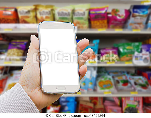 left asian hand with pullover holding blank screen smart phone on blurred background of various brand of Dried fruits and nuts in packaging for sale on supermarket stand or shelf