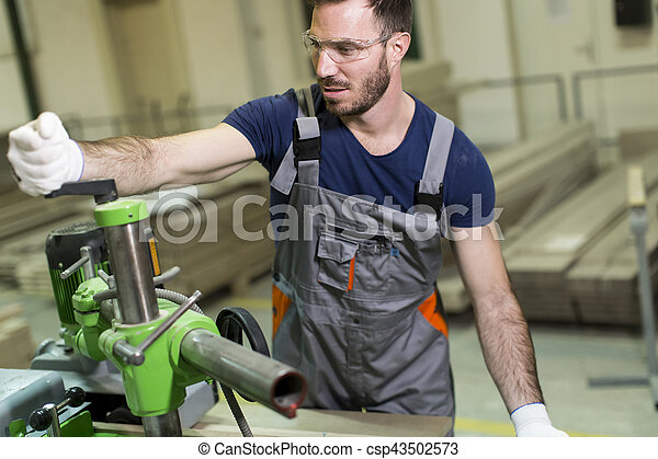 Young man works in a factory for the production of furniture
