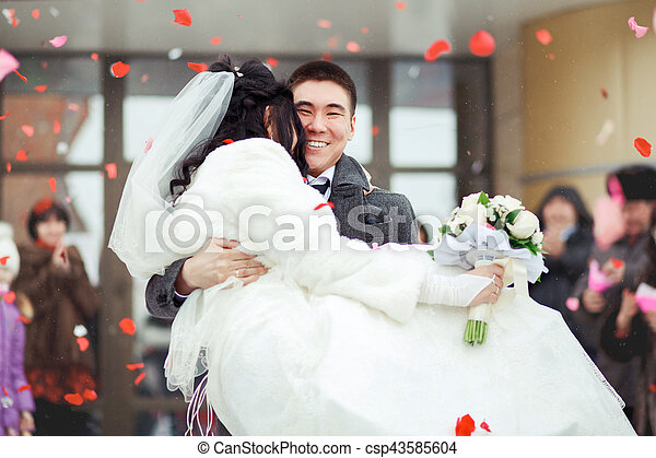 The groom carrying bride in his arms, the crowd throws petals and rice. Happy wedding. - csp43585604