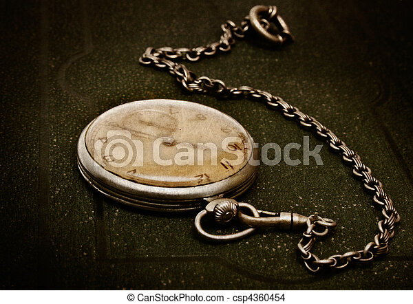 Old clock with chain lying on rough green surface - csp4360454
