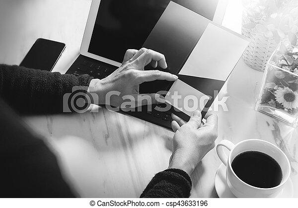 Businessperson Hands holding New Gift Card or Credit card,digital tablet computer dock keyboard,smart phone on marble desk,black white