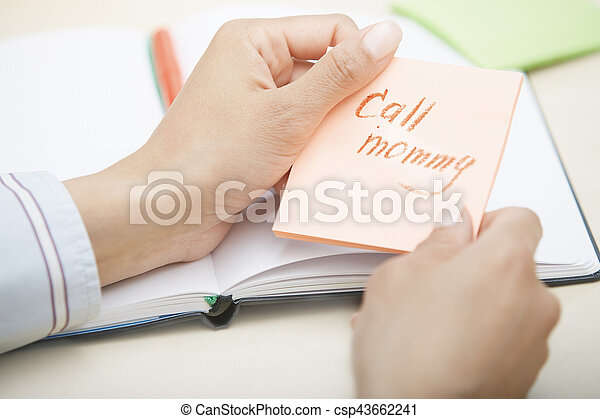 Hands holding sticky note with Call mommy text