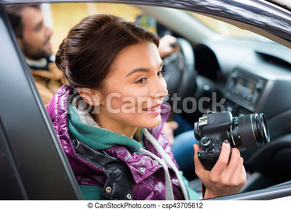 Smiling brunette woman holding photo camera and looking in car window with blurred male driver on background