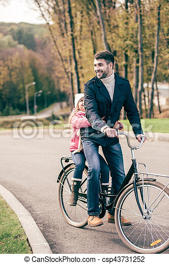 Happy father carrying his adorable little daughter on bike in autumn park