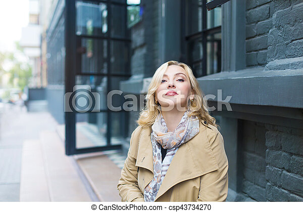 Middle age women goes through the city and smiles. Happiness concept.