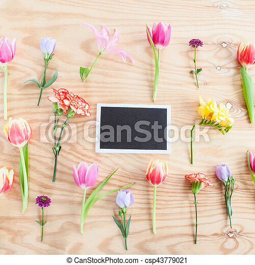 Variety of fresh spring flowers on rustic wooden background