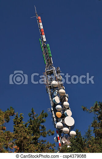 Telecommunication mast with microwave links and TV transmitter antennas over a blue sky. - csp4379088