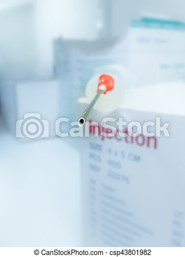 Injection needle on a box with medical supply. Extreme shallow depth of field with blurred background.