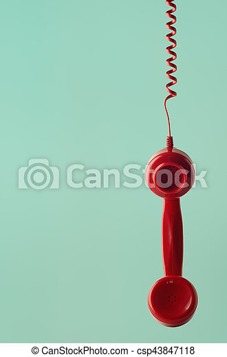 A British 60s and 70s style retro red telephone receiver, facing front and hanging by spiral cord against aqua background.
