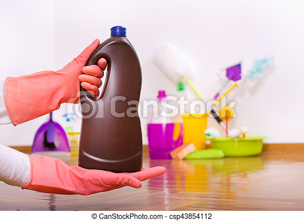 Close up of hand with protective glove holding bottle of chemicals for wooden floor mopping above parquet and other cleaning tools in background