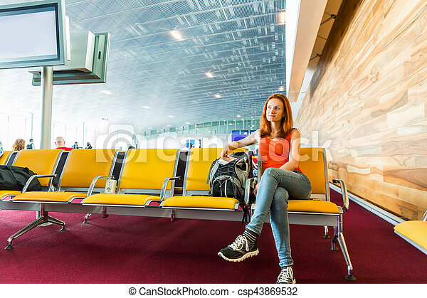 Young female traveller with ticket in her hands sitting on the chair in waiting hall. Suitable for bus, railway, metro station.