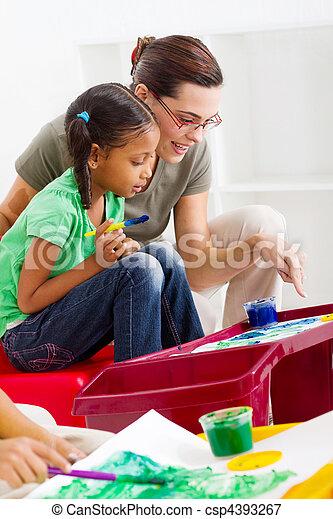 caring teacher help preschool girl  - csp4393267