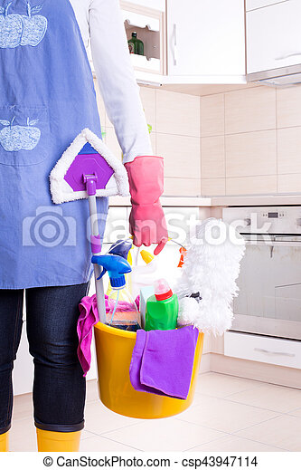 House keeper with apron and rubber gloves holding basket full of cleaning supplies and equipment in front of kitchen