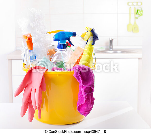 Plastic bucket full of cleaning supplies and equipment on white table in front of kitchen cabinets