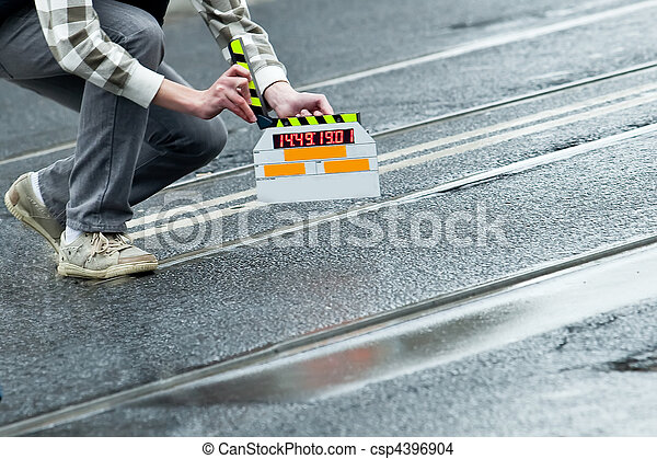 Making movie and slate holding by a man on wet road  - csp4396904