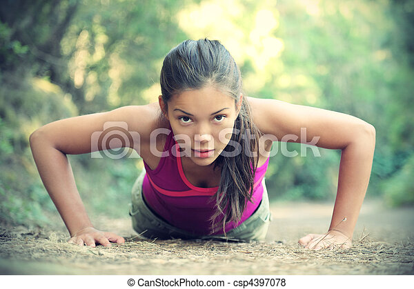 Exercise woman training doing push-ups outside - csp4397078