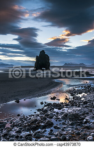A landmark beach in Iceland called Dinosaur Rock protrudes 50 feet out of the shallow water during an early morning sunrise.