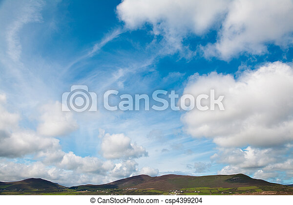 bright blue sky white clouds over green Irish hills - csp4399204