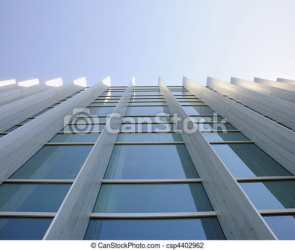 Exterior windows of a commercial office building looking up from the ground with blue sky refected in windows - csp4402962