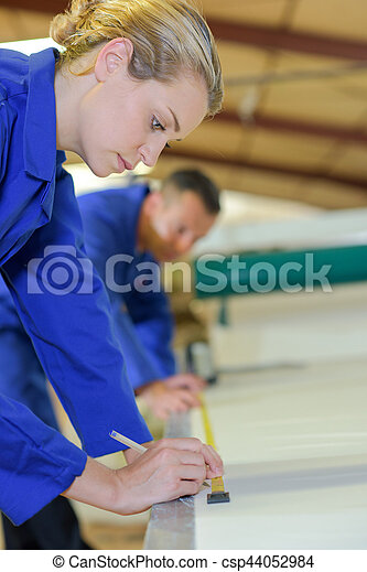 Female worker measuring and marking material - csp44052984