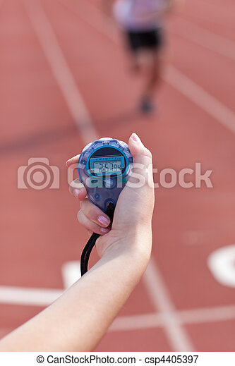 Close-up of a woman holding a chronometer to measure performances of a sprinter in a stadium - csp4405397