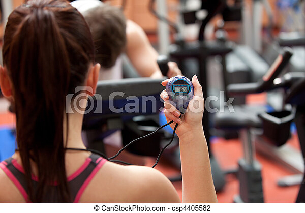 Young woman holding a chronometer and man doing physical exercise in a fitness center - csp4405582