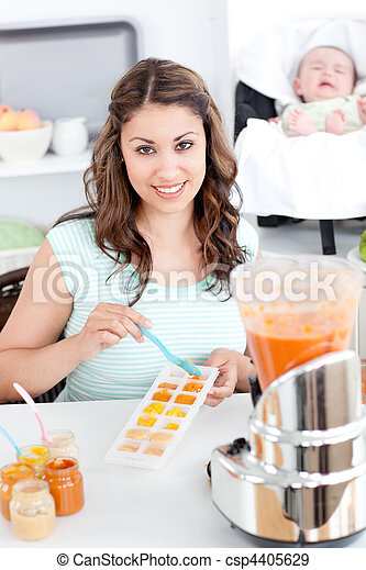 Caring mother preparing food for her lovely baby in the kitchen - csp4405629