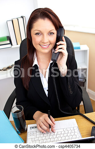 Self-assured businesswoman talking on phone and using her laptop at her desk in her office - csp4405734