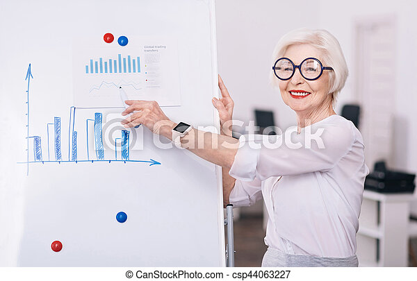 Coaching young generation. Happy creative attentive businesswoman standing near the white board in the office and pointing on it while smiling and looking at the audience