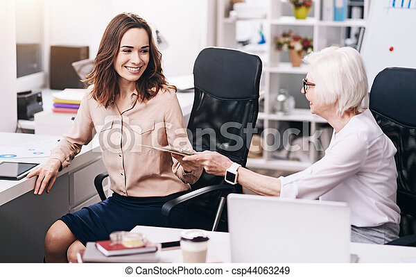 Sharing experience with colleague. Charming happy positive colleagues sitting in the office and working while expressing happiness and sharing documents