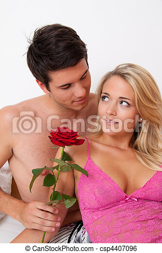 Romantic couple in bed with Rose. Marry the man. - csp4407096
