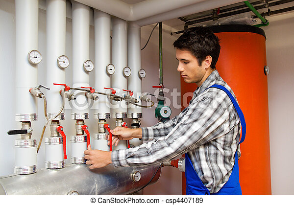 Heating engineer in a boiler room for heating system - csp4407189