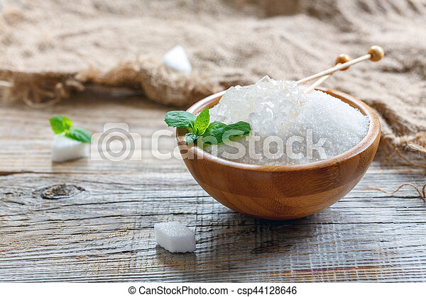 White figured sugar and crystal sugar sticks in a wooden bowl on the old table, selective focus.
