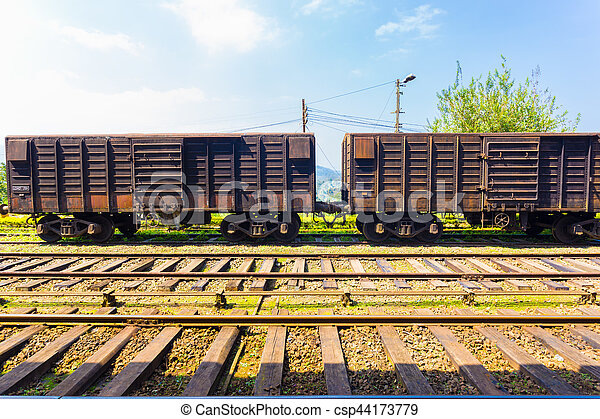 Side view of an old stationary rusted cargo carriage car sitting parked on train tracks, part of Sri Lanka Railways, on a blue sky day. Horizontal