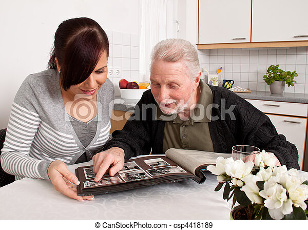Woman looks at a photo album with seniors - csp4418189