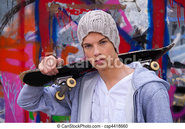 Cool-looking young man in front of graffiti - csp4418660