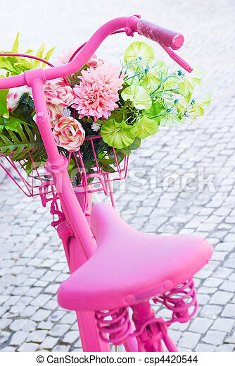 Detail of a pink painted bicycle with a basket with flowers and leaves
