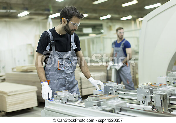 Two male workers working in furniture industry and creating custom furniture