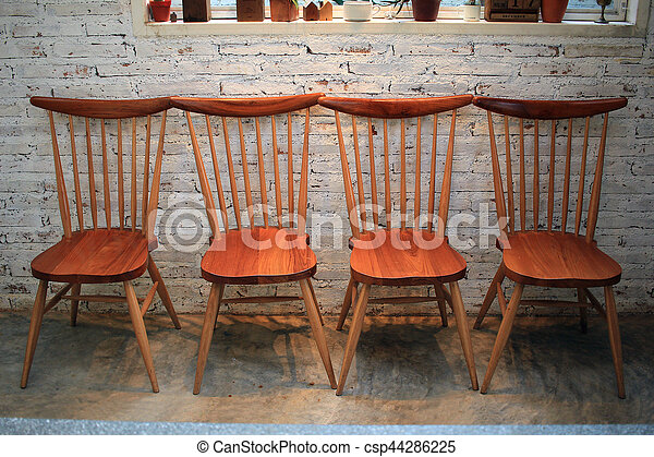Wooden chairs in room with brick wall - csp44286225