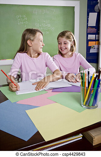 Girls in classroom doing schoolwork, writing - csp4429843