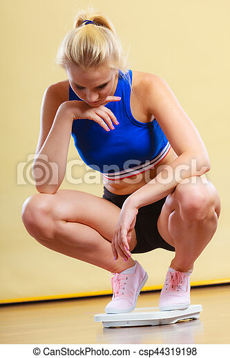 Slimming diet weight loss. Upset unhappy young sporty woman on weight scale. Healthy lifestyle concept.