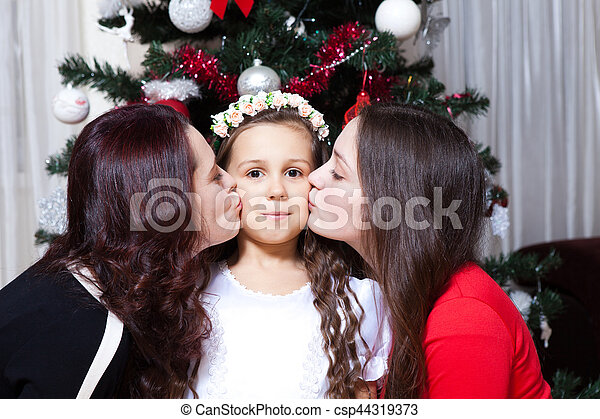 people, motherhood, family, christmas and adoption concept - happy mother and daughter hugging and kissing at home