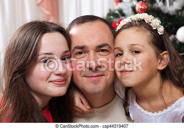 people, motherhood, family, christmas and adoption concept - happy father and daughter hugging and kissing at home