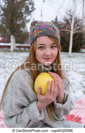 Funny hipster girl whith a pomelo in knitted sweater and cap. Trendy in winter.