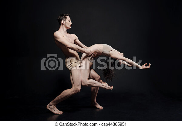 Art performance in motion. Pleasant flexible skilled dancers standing isolated in the black colored studio and taking part in the art performance while showing their ability to keep the balance