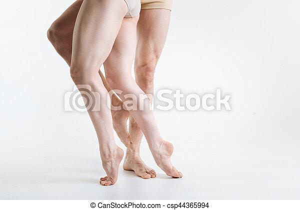 Elegant ballet dancers legs . Gracile elegant athletic ballet dancers legs located in the white colored studio and demonstrating dancing pa
