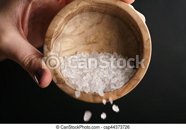 coarse sea salt crystal falling from bowl, closeup photo