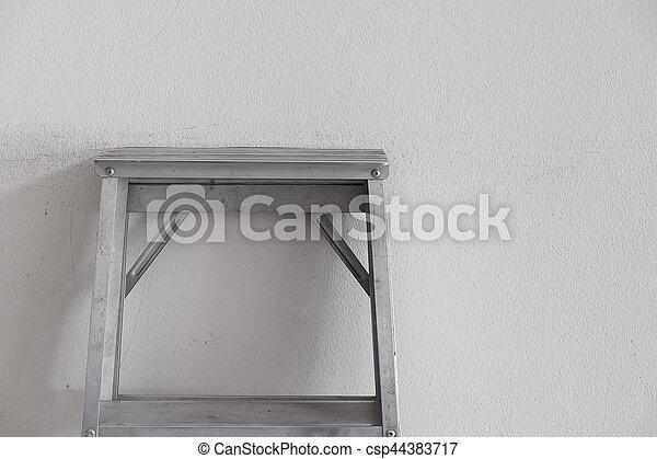 Aluminum ladder on the gray wall, room interior.